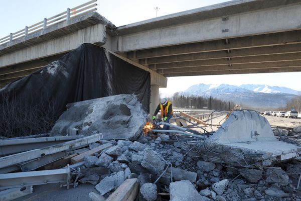 Bill Taylor of Sandstrom & Sons cuts steel with a torch as workers demolish the damaged girder after removing it in two pieces from the Artillery Road overpass in Eagle River early Sunday morning, March 25, 2018. Reopening of the southbound Glenn Highway is on schedule for Monday morning according to the Alaska DOT & PF. (Bill Roth / ADN)