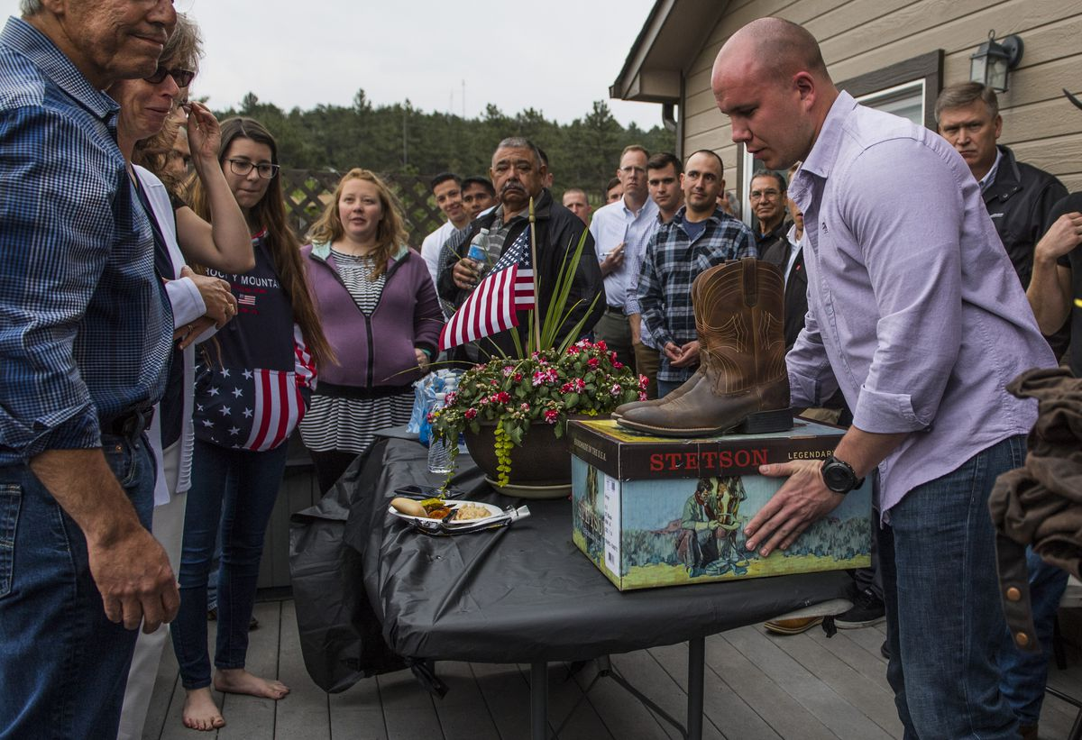 Army Staff Sgt. Doug Campbell, right, presents Bob and Donna Conde, left, with their son, Army Spc. Gabriel D. Conde's cowboy boots during a family and friends gathering at the Conde's home on May 11, 2018 in Loveland, Colo. (Washington Post photo by Ricky Carioti)