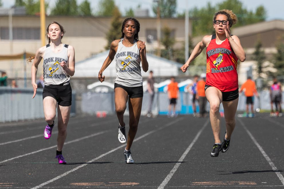 From left, Chugiak's Shaylee Griffin, South's Paige Searles, and Delta's Hailey Williams compete in the 100 meter dash at the Brian Young Invitational Friday, May 31, 2019 at West High. (Loren Holmes / ADN)