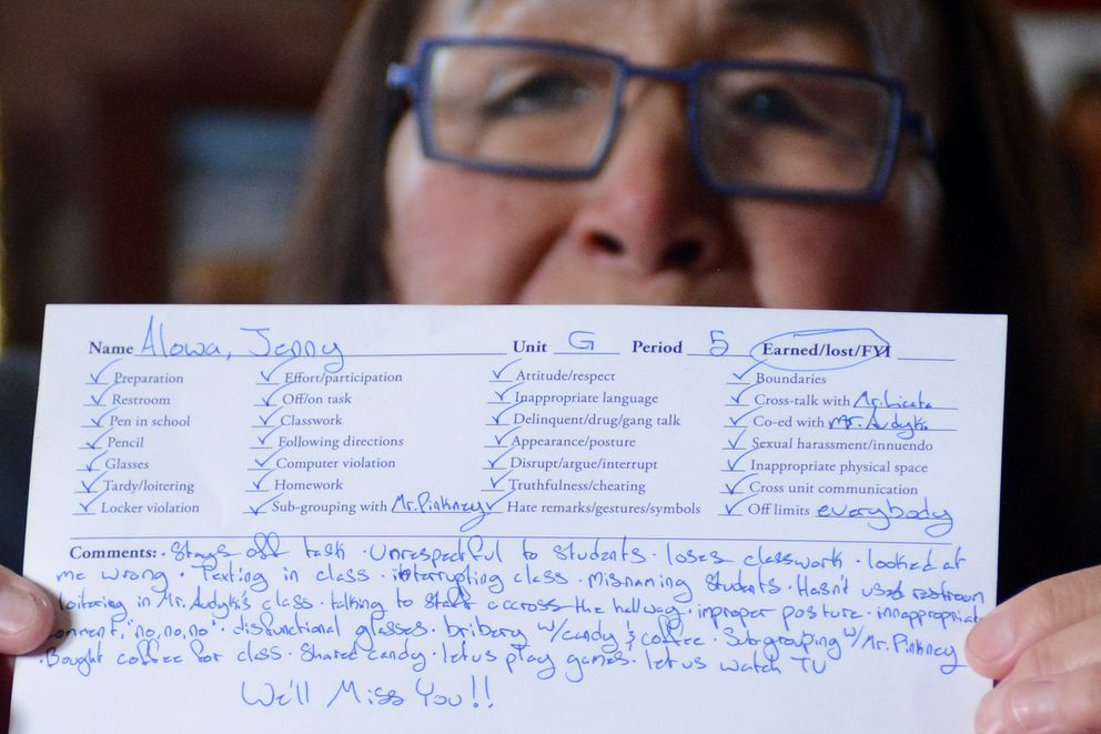 Jenny Alowa holds a humorous point slip, usually filled out for students, that her students made for her when she retired from a 25-year teaching career at McLaughlin Youth Center. (Erik Hill / Alaska Dispatch News)