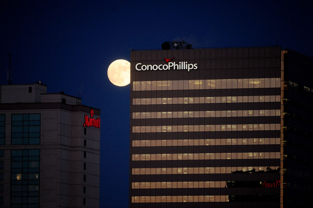 The nearly full moon rises over downtown Anchorage next to the ConocoPhillips building at sunset on Monday, February, 2, 2015.