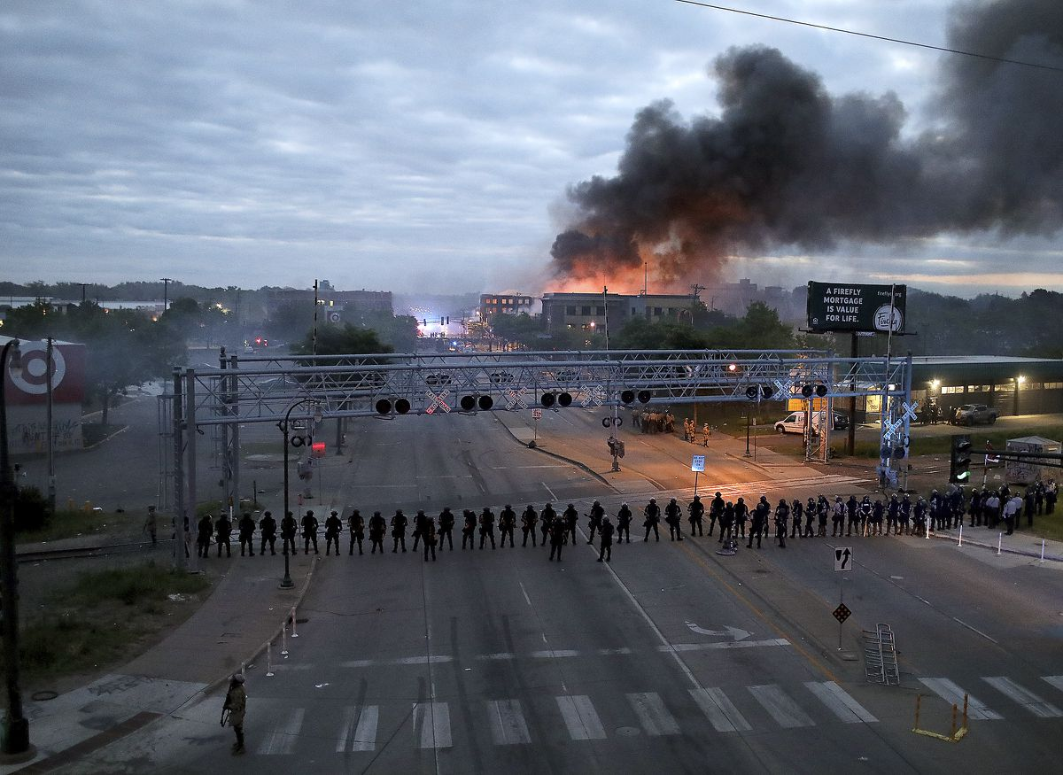 Law enforcement officers stand in formation along Lake Street near Hiawatha Ave. as fires burned after a night of unrest and protests in the death of George Floyd early Friday, May 29, 2020 in Minneapolis. Floyd died after being restrained by Minneapolis police officers on Memorial Day. (David Joles/Star Tribune via AP)