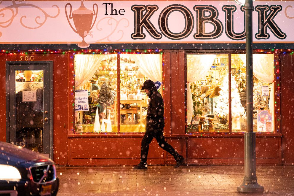 A person walks past The Kobuk as snow falls on Nov. 30, 2019. (Loren Holmes / ADN)
