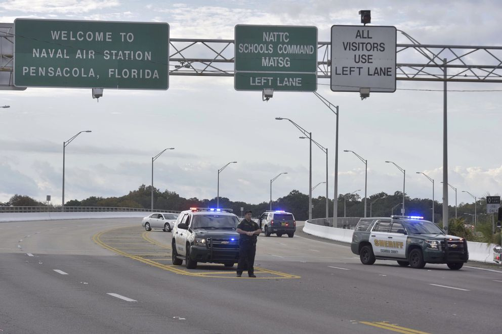 Police vehicles block the entrance to the Pensacola Air Base, Friday, Dec. 6, 2019 in Pensacola, Fla. The US Navy is confirming that a shooter is dead and several injured after gunfire at the Naval Air Station in Pensacola. (Tony Giberson/ Pensacola News Journal via AP)