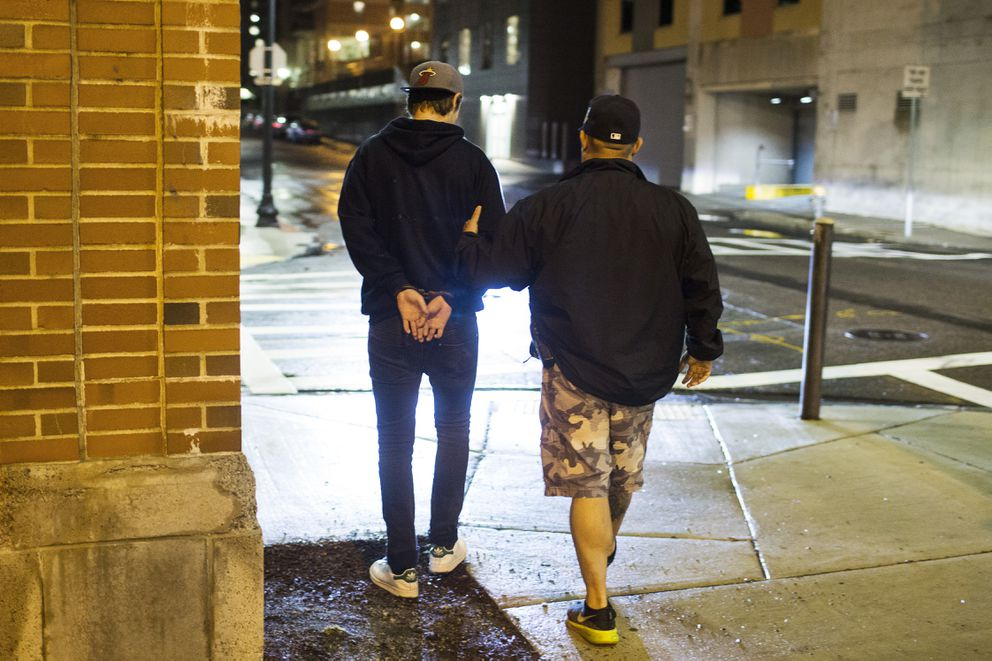 Sgt. Larry Cuzzi of the Boston University Police, with a 19-year-old man who was caught urinating on a building in Boston, on Oct. 1. (Adam Glanzman / The New York Times)