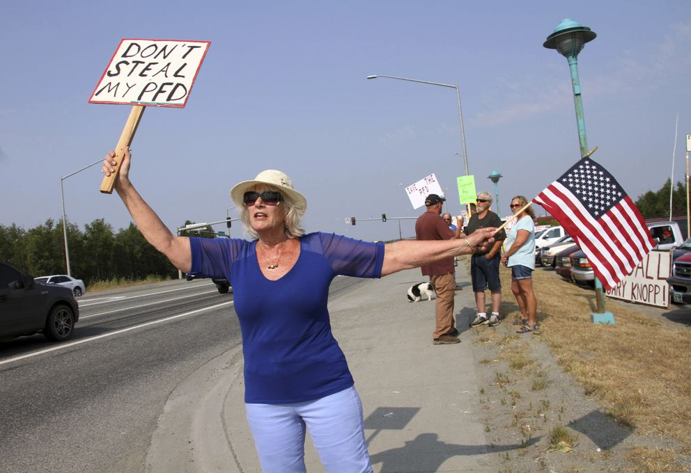 Katherine Hayes waves a flag and a sign urging Alaska lawmakers to fund a full oil wealth fund check, known locally as the PFD or Permanent Fund Dividend, Monday, July 8, 2019, in Wasilla, Alaska. Some Alaska lawmakers are meeting in Wasilla July 8 instead of Juneau, where state House and Senate leadership have decided to hold the special session, called to determine the amount of this year's check. (AP Photo/Mark Thiessen)