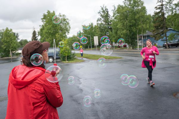 Mary Casey blows bubbles as her daughter, Mary McCormick, runs past during a virtual Run for Women Saturday, June 20, 2020 in Eagle River. About 40 participants ran or walked the challenging 5-mile course. (Loren Holmes / ADN)