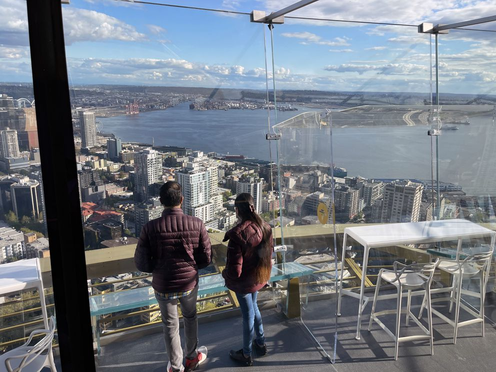 A couple pauses to look out the all-new floor-to-ceiling glass windows at the top of the Space Needle in Seattle. (Photo by Scott McMurren)