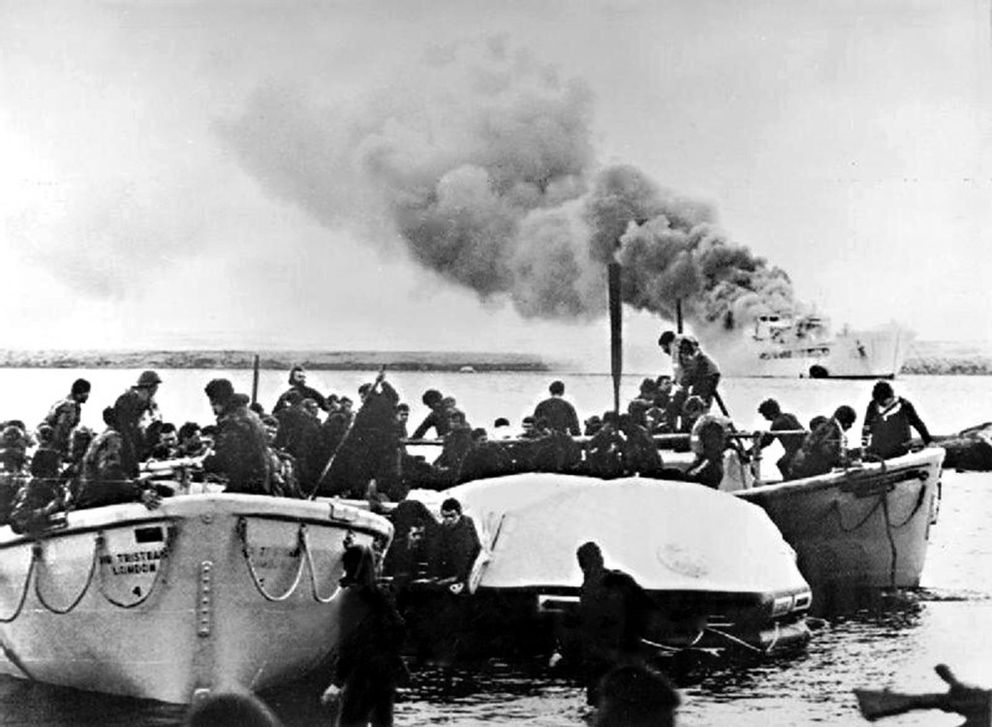 Lifeboats carrying survivors from an Argentine bombing run arrive near Fitzroy as the supply ship Sir Galahad burns in the distance. (Crown Copyright)