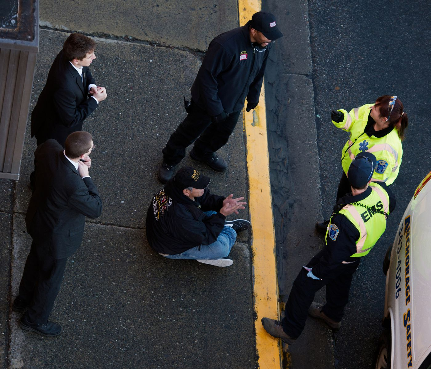 "Anchorage Safety Patrol staff members Pam Garner, top right, and Garrett Sey talk with security staff outside the Hotel Captain Cook before transporting a man to the Anchorage Safety Center. ""The worst part is not being able to help them, and seeing that a lot of them do want to get help but they don't want to reach out,"" Garner said. Photographed on Wednesday, November 19, 2014. Marc Lester / ADN"