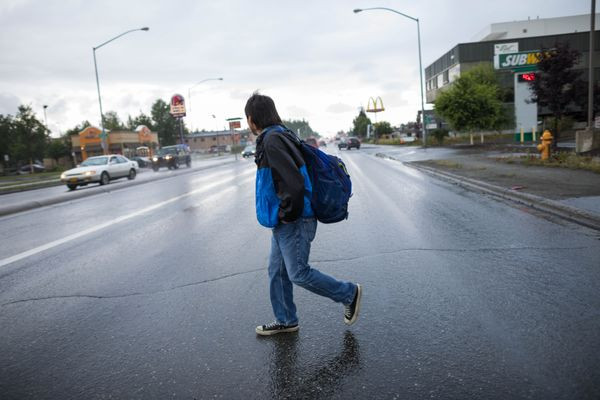 Melvin Ivanoff crosses Tudor Road, walking to the bus stop before a job interview Thursday, Aug. 10, 2017. Ivanoff recently got out of jail and is trying to stay sober and find a steady job. (Loren Holmes / Alaska Dispatch News)