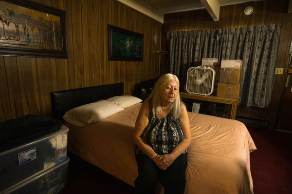 Portia Belshe sits on her bed at the Mush Inn Motel on Wednesday, Nov. 14, 2018. Belshe moved into the $800 per month room in May and has had problems with bedbugs and cockroaches ever since. (Loren Holmes / ADN)