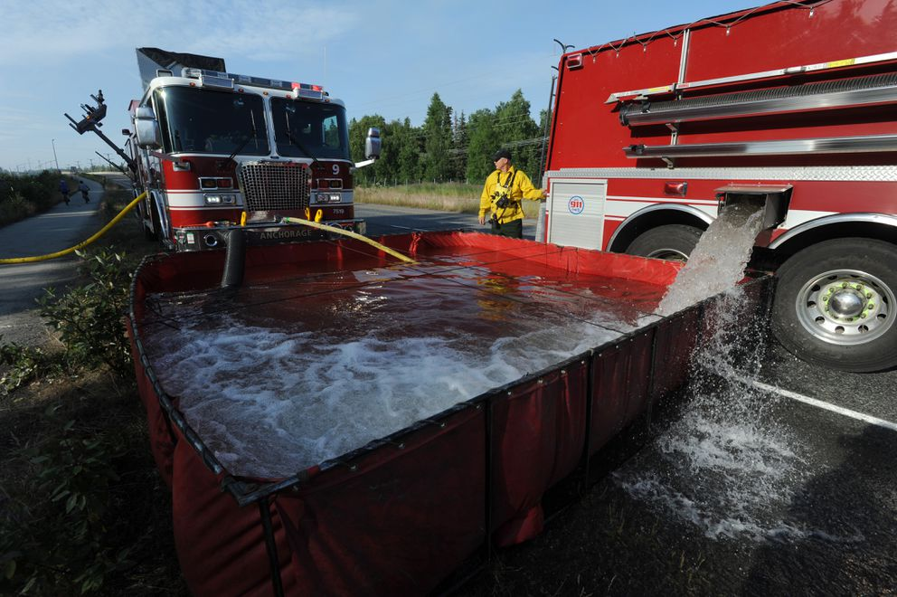 AFD Engineer Cal Lauwers adds water to a Fol-Da-Tank from Tender 9 as AFD and wildland firefighters battled the brush fire from Elmore Road on Tuesday, July 2, 2019. (Bill Roth / ADN)