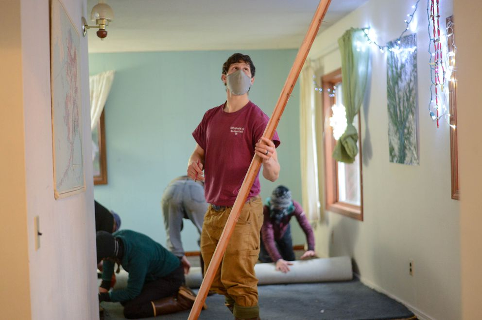 Ben Bard and other friends remove water-damaged carpet and fixtures from the home of Lindsey Edgar on Saturday morning, Dec. 5, 2020. Edgar woke on Wednesday to two feet of water and waves in her living room. She evacuated, but as friends arrived to help her clean up, was told that her insurance policy doesn't cover floods. (James Brooks / ADN)
