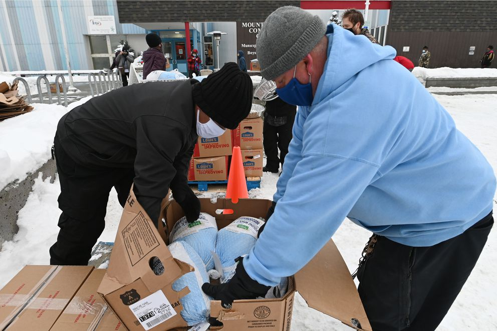 Heriberto Torres and David Barney unpack a box of frozen turkeys during the Thanksgiving Blessing food distribution event at the Mountain View Community Center Boys and Girls Club on Monday, Nov. 23, 2020. (Bill Roth / ADN)