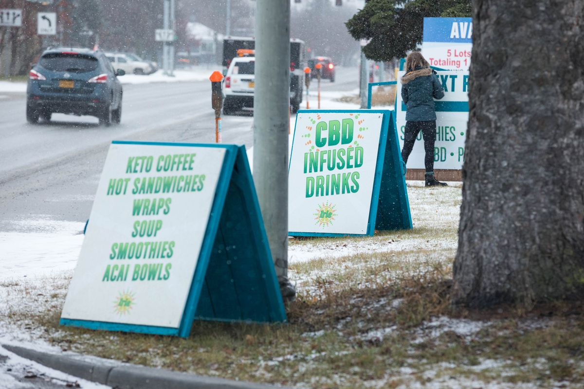 Irie owner Marie Gaze fixes a sign outside her smoothie shack in downtown Anchorage on Nov. 28. Irie sells drinks infused with CBD, a non-intoxicating cannabis extract. (Loren Holmes / ADN)