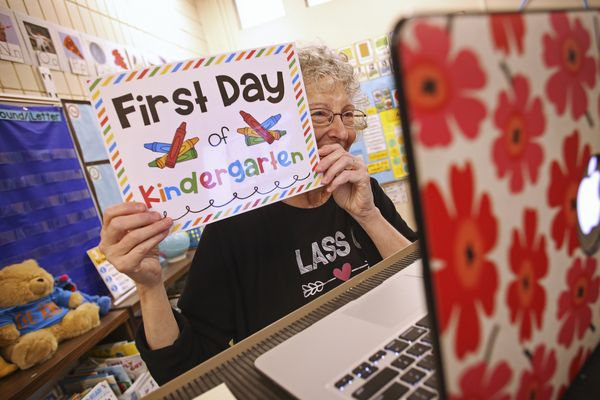Karen Gordon holds up a first-day-of-kindergarten sign for her students in the first class of the school year over Zoom from her empty classroom at Northwood Elementary School in Anchorage on Aug. 25, 2020. She had each student create their own first-day-of-kindergarten sign to show on the first day. (Emily Mesner / ADN)