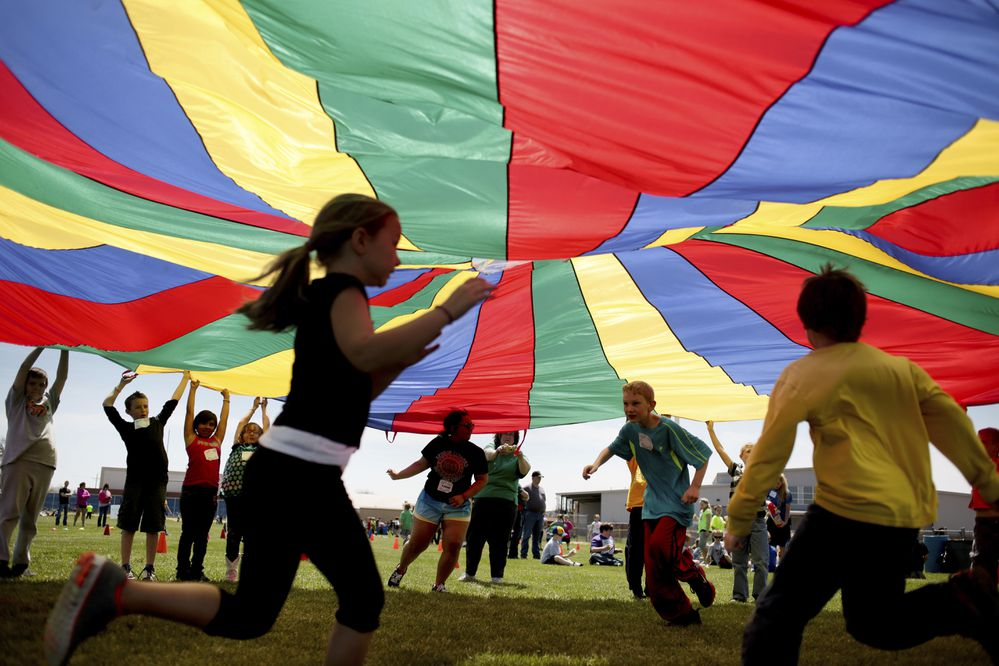 FILE - In this Thursday, April 25, 2013 file photo, elementary school third graders run under a rainbow colored tarp during the 15th Annual Kansas Kids Fitness Day, in Hutchinson, Kan. New federal guidelines released on Monday, Nov. 12, 2018, advise that children as young as age 3 should move more, sit less and get more active, and that any amount and any type of exercise helps health. (Aaron Marineau/The Hutchinson News via AP)