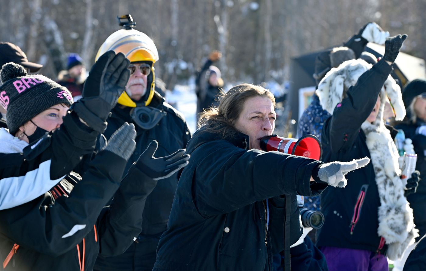 Cindy Hite, center, cheers on mushers with a megaphone at the start of the Iditarod at Deshka Landing in Willow. (Marc Lester / ADN)