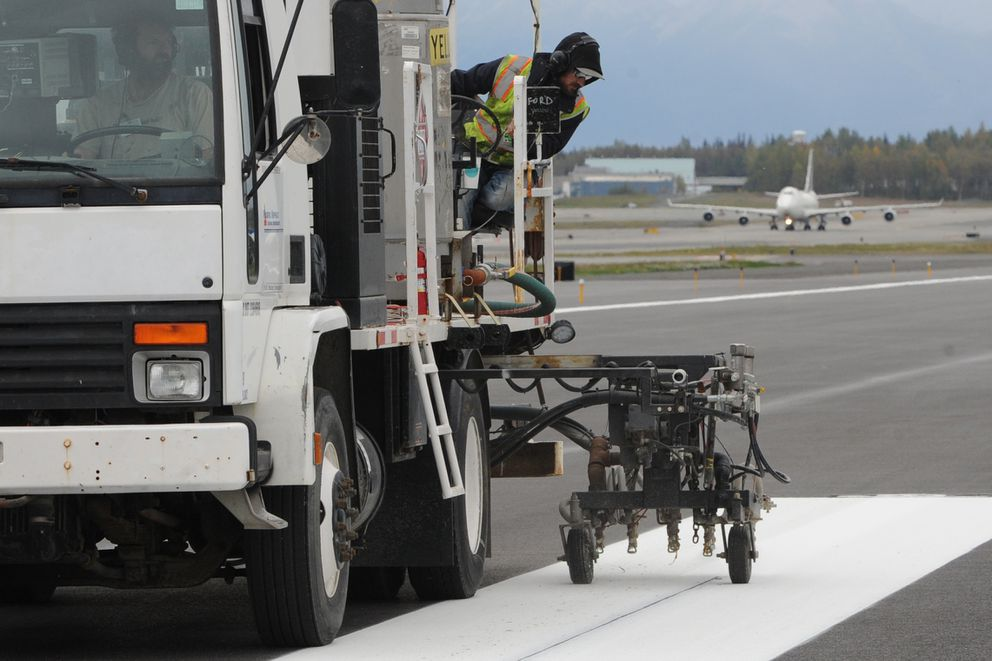 Douglas Duff of Pacific Asphalt paints runway markings as construction work on Runway 15-33, the north-south runway at Ted Stevens Anchorage International Airport winds down.