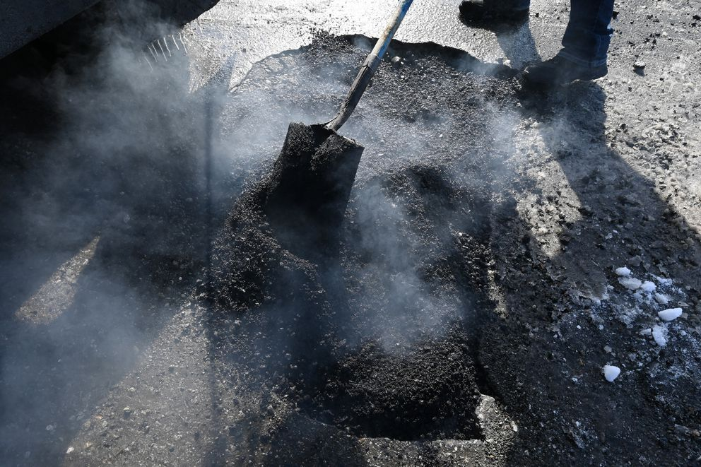Steam rises from hot asphalt used to fill a pothole at 26th Avenue and Minnesota Drive Thursday, April 1, 2021. (Bill Roth / ADN)