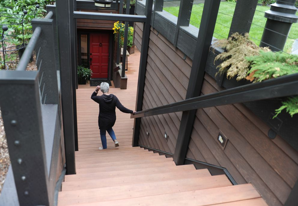 Marnie Isaacs walks down the stairs to the front door. (Anne Raup / ADN)