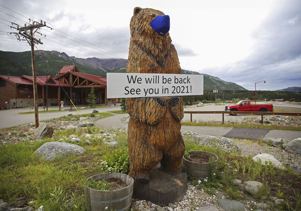 A sign on a masked wooden bear announces the closure of the Denali Princess Wilderness Lodge in Glitter Gulch outside Denali National Park and Preserve on July 12, 2020. (Emily Mesner / ADN)
