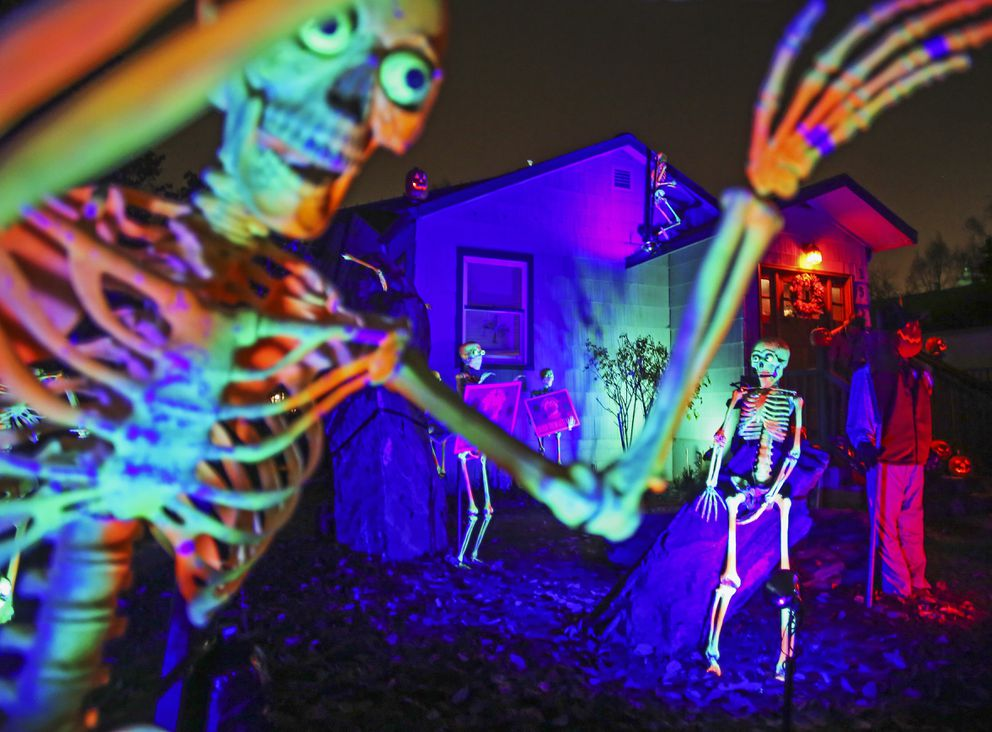 Moving skeletons, constructed from windshield wipers, individually carved foam pumpkins and orange lights decorate the outside of Owen Carey's home near West 15th Avenue and H Street in Anchorage on Oct. 28, 2020. (Emily Mesner / ADN)