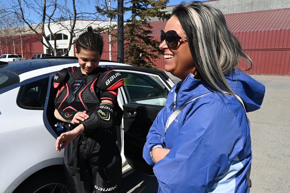 Tavian Mukaabya takes off his new gear as he and mom Tiffany Mukaabya talk in the Dempsey Anderson parking lot. First responders cut apart Tavian's old gear when he was injured in a Feb. 25 car accident. (Bill Roth / ADN)