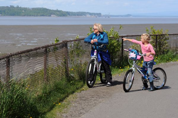 Bree Dollick, 8, of San Diego, right, points out snow-covered mountains to grandmother Cheryl Dollick of Anchorage as they pedal the Tony Knowles Coastal Trail on Monday afternoon, May 23, 2016, near Westchester Lagoon. Their families were picnicking, kayaking, cycling and using the playground at the lagoon.