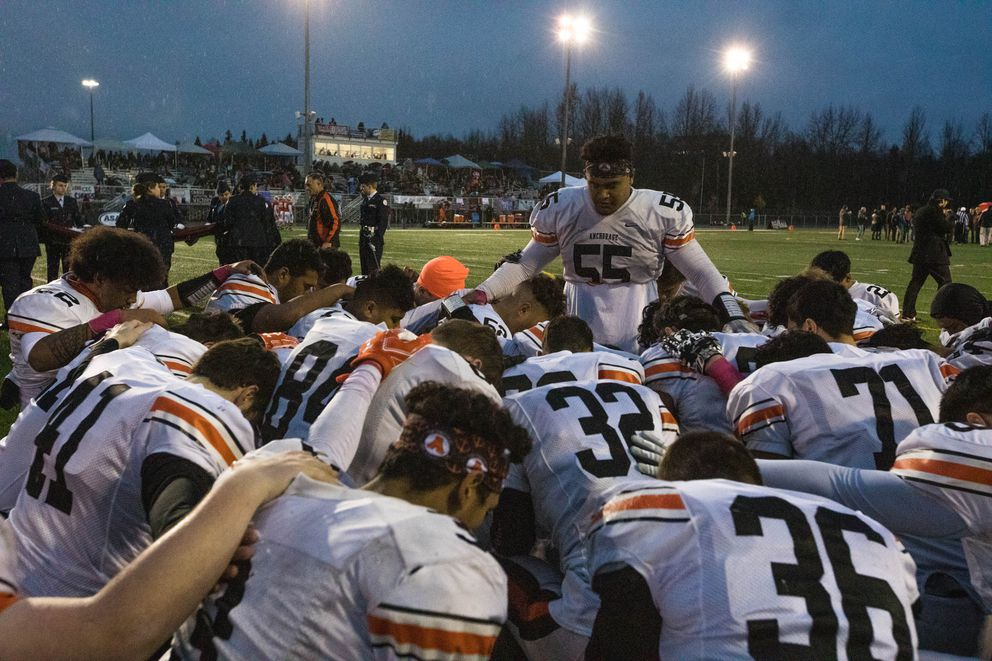West High senior Fiavaai Faalata leads his teammates in a prayer before last year's Division 1 state championship game against East. East won won 35-6. (Loren Holmes / ADN)