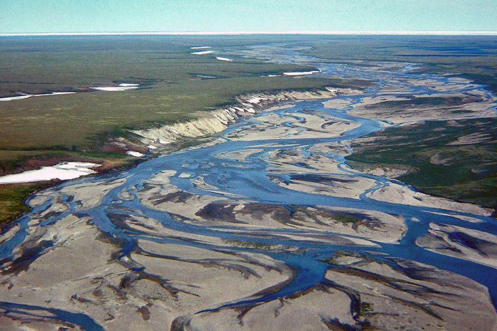 The Jago River flows north to the Arctic Ocean and its ice pack visible in the distance in the 1990s. Geologist Gil Mull said the yellowish gray weathering bluffs on the left had a strong gassy, oily odor on a warm day. (Gil Mull / Alaska Division of Geological and Geophysical Surveys)