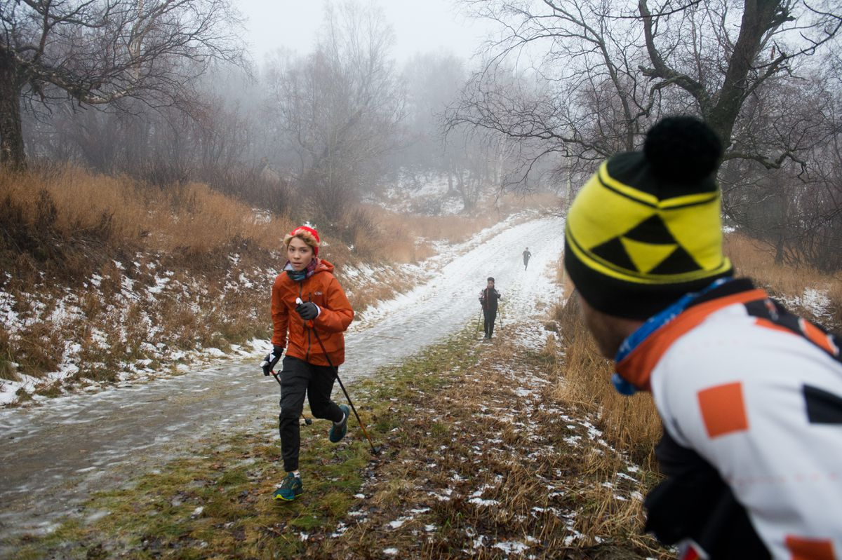 West High School cross country skiing coach Anson Moxness, right, instructs his athletes as they work out at Kincaid Park on Tuesday. Lacking much snow on the ground, the team ran with their ski poles. Head coach Anson Moxness said it's been one of the latest starts to the ski season in his seven years as coach. (Marc Lester / ADN)