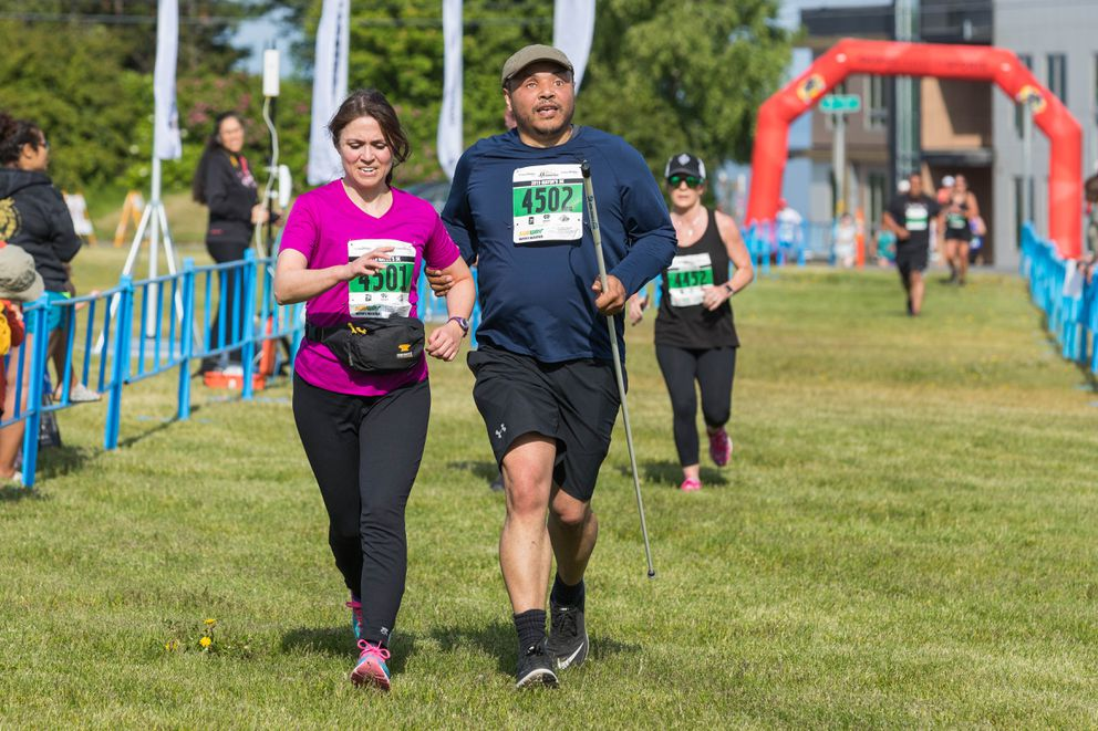 Pamela Gebert and Nate Kile run toward the finish line in the 5K. Gebert guided Kile, who is blind, through the course. (Loren Holmes / ADN)