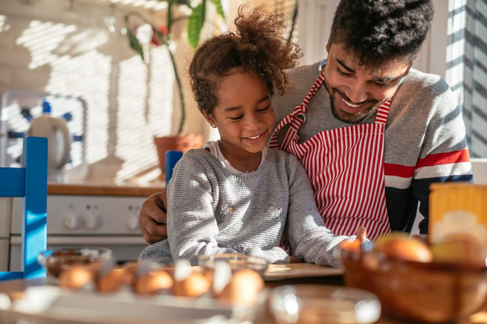 African american father and daughter preparing to bake.