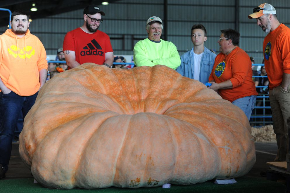 Dale Marshall, center, of Anchorage stands near his pumpkin that broke his previous state record by more than 600 pounds. (Bill Roth / ADN)