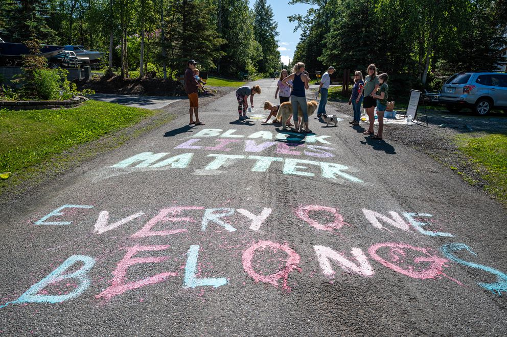 Residents of Zenith Street and the surrounding neighborhood paint messages on their street before DeWayne Ingram and his supporters run by on Saturday. (Loren Holmes / ADN)