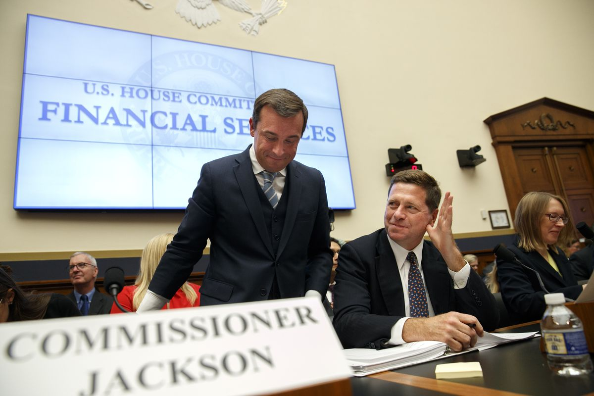 In this Sept. 24, 2019, file photo, SEC Chairman Jay Clayton, center, waves to a commissioner as he takes his seat between SEC Commissioners Robert Jackson Jr., left, and Hester Peirce, at the start of a House Financial Services Committee hearing on Capitol Hill in Washington. (AP Photo/Jacquelyn Martin, File)
