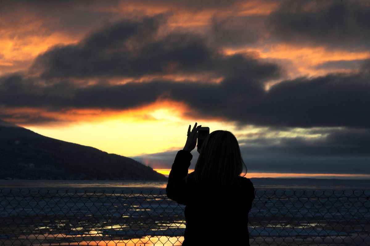 Christine Moss stopped to capture the sunset while driving southbound on the Seward Highway along Turnagain Arm on Thursday afternoon, Dec. 20, 2018.. (Bill Roth / ADN)