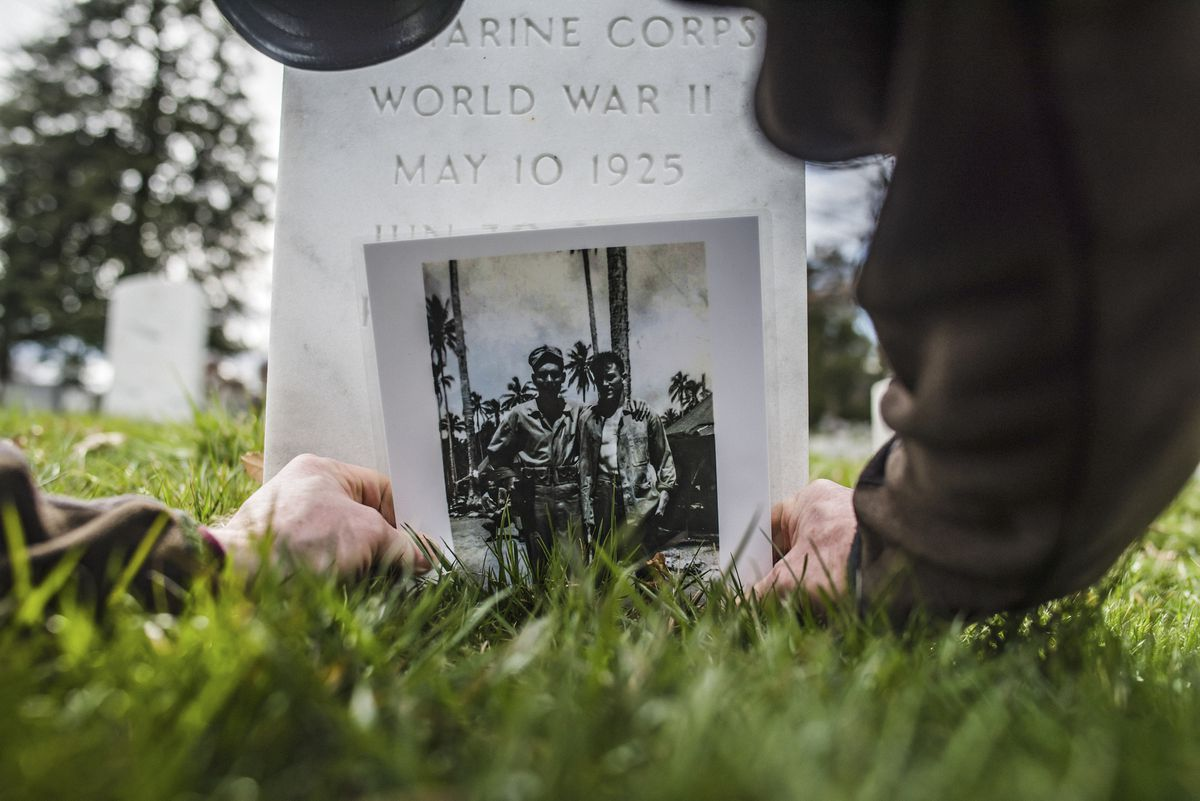 Dale Maharidge places a photo showing his father Steve Maharidge with fellow WWII Marine and friend Herman Mulligan, at the father's tombstone in Arlington National Cemetery, in Virginia, April 1, 2018. The search for Private First Class Herman Mulligan, who died on Okinawa during World War II, started with a blood-flecked Japanese flag that Maharidge found among his father's things after he died. (Ryan Christopher Jones/The New York Times)