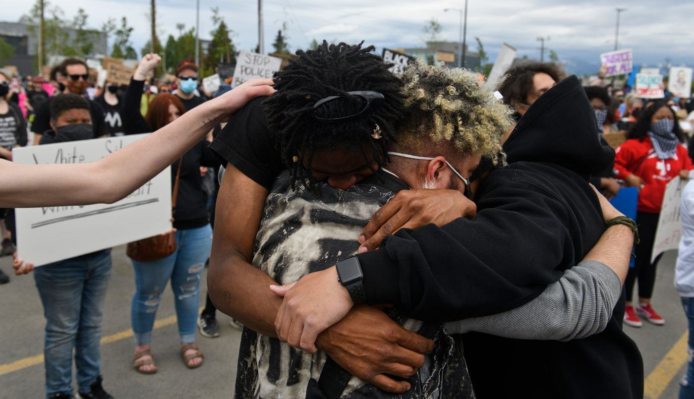 Protesters hug at the Midtown Mall rally. (Marc Lester / Anchorage Daily News)
