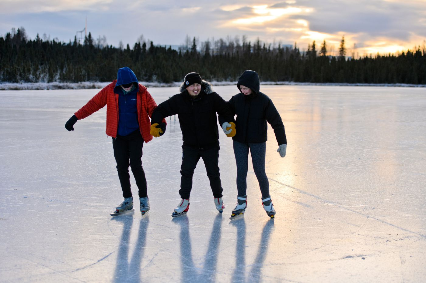Will Ames gets help staying upright while learning to ice skate on Goose Lake in Anchorage. At left is John Freeman and at right Lindsey Freeman. (Marc Lester / ADN)