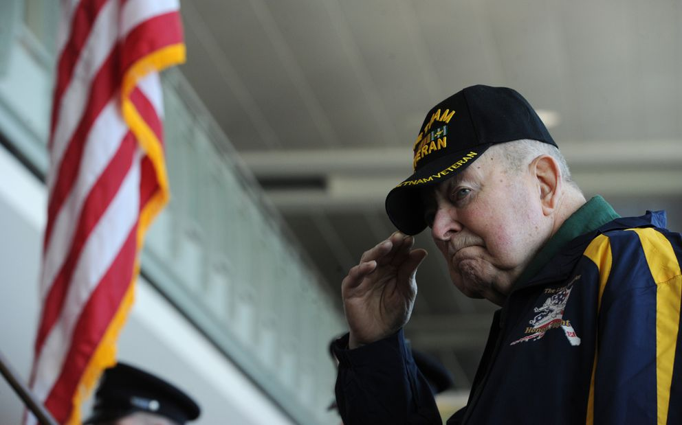 U.S. Army veteran Paul Slooter, who served two tours of duty in Vietnam, salutes during the singing of the national anthem before the departure of the Last Frontier Honor Flight on Tuesday. (Bill Roth / ADN)