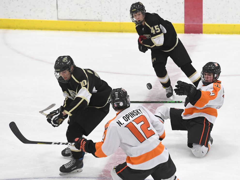 From left, South's Logan Maddox, West's Nicko Opinsky, South's Reed Donald and West's Ian Keim surround the puck. (Photo by Bob Hallinen)