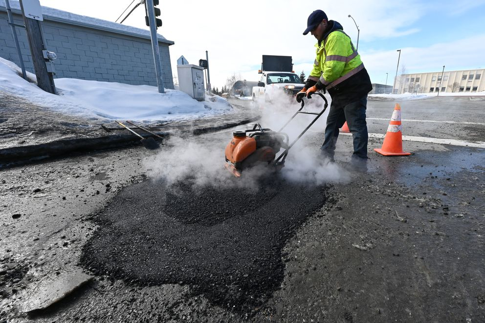 City street maintenance worker Chris Bean compacts hot asphalt after filling a large pothole at 26th Avenue and Minnesota Drive Thursday, April 1, 2021. (Bill Roth / ADN)