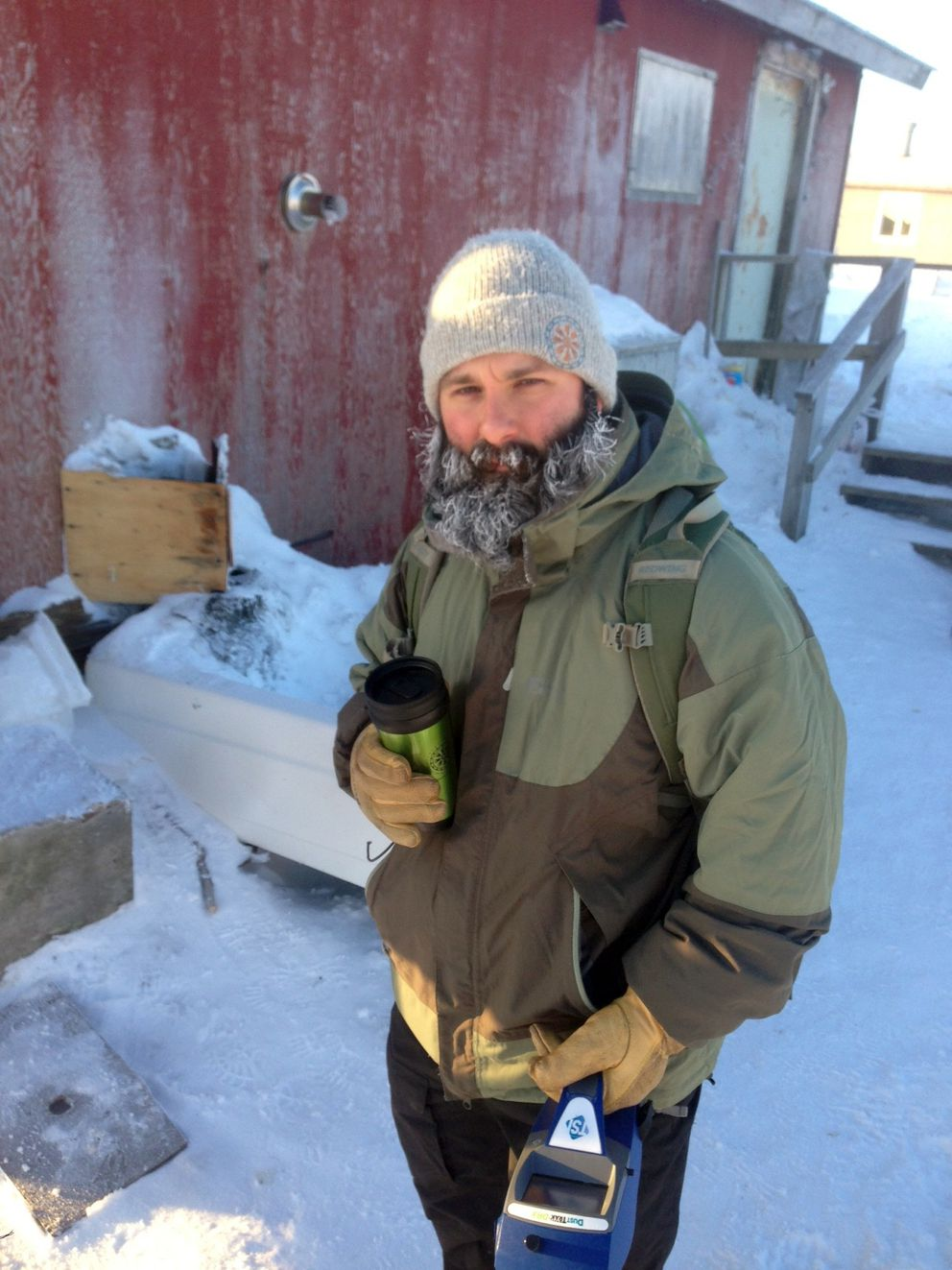 Salkoski holds an air monitor outside a home in Southwest Alaska during the winter of 2013. (Courtesy A.J. Salkoski / ANTHC)