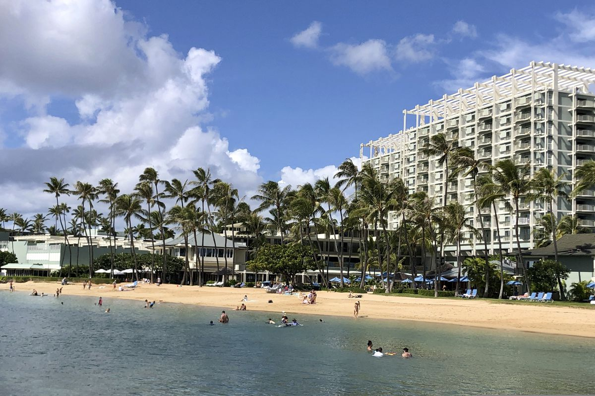 People are seen on the beach and in the water in front of the Kahala Hotel & Resort in Honolulu, Hawaii, on Nov. 15, 2020. (Jennifer Sinco Kelleher / AP)