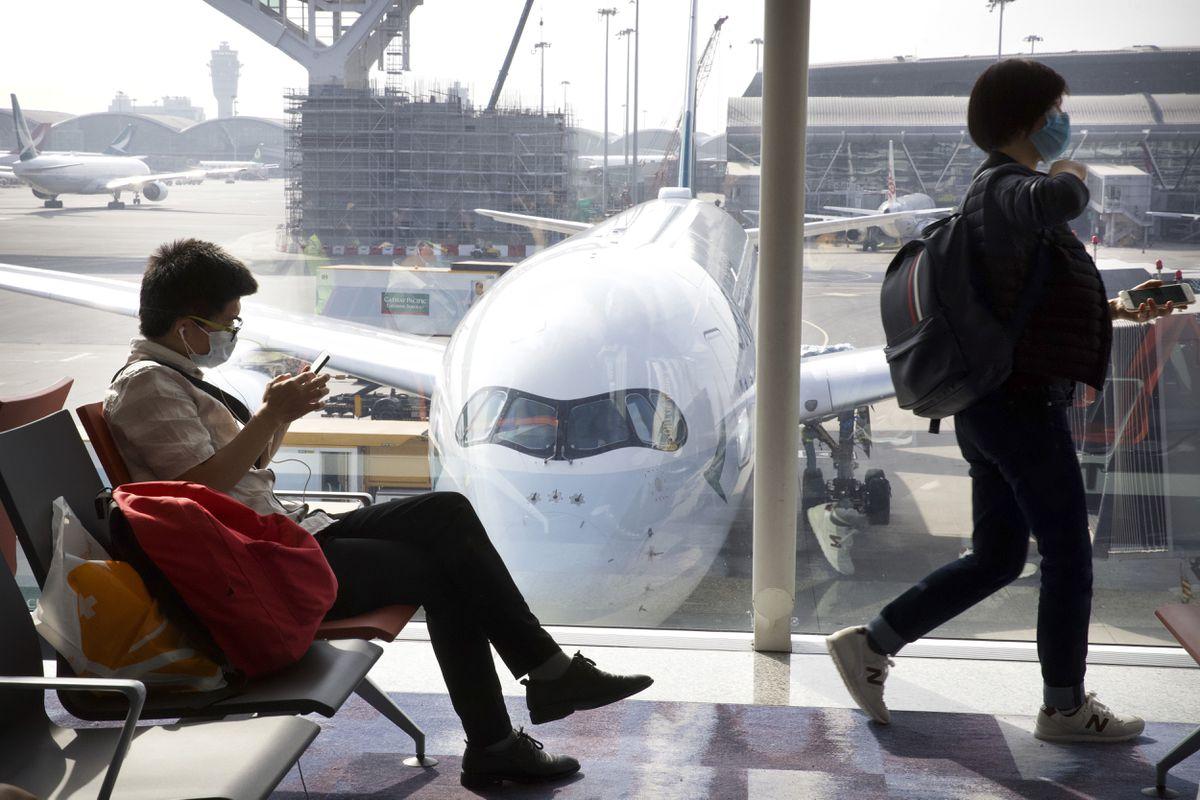 Travelers wear face masks as they wait their flight at Hong Kong International Airport in Hong Kong, Tuesday, Jan. 21, 2020. (AP Photo/Ng Han Guan)