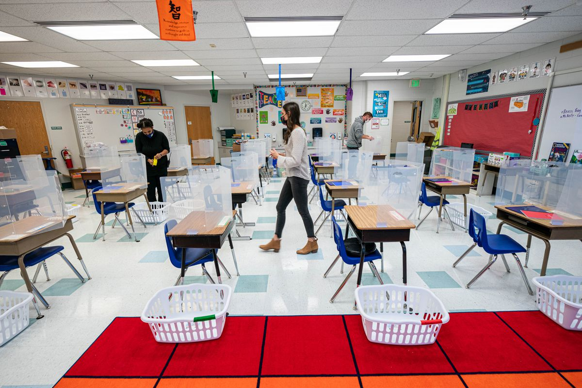Teaching assistant Fherron Hines, left, and substitute teacher David Barger, right, help second-grade teacher Kristin Soult, center, prepare her classroom in the former art room at Creekside Park Elementary on Friday, Jan. 15, 2021. (Loren Holmes / ADN)