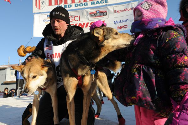 Iditarod musher Dallas Seavey poses with his lead dogs Reef and Tide while his daughter reaches out to pet one at the finish line of the 2017 Iditarod Trail Sled Dog Race on Tuesday, March 14, 2017. (Bob Hallinen / Alaska Dispatch News)